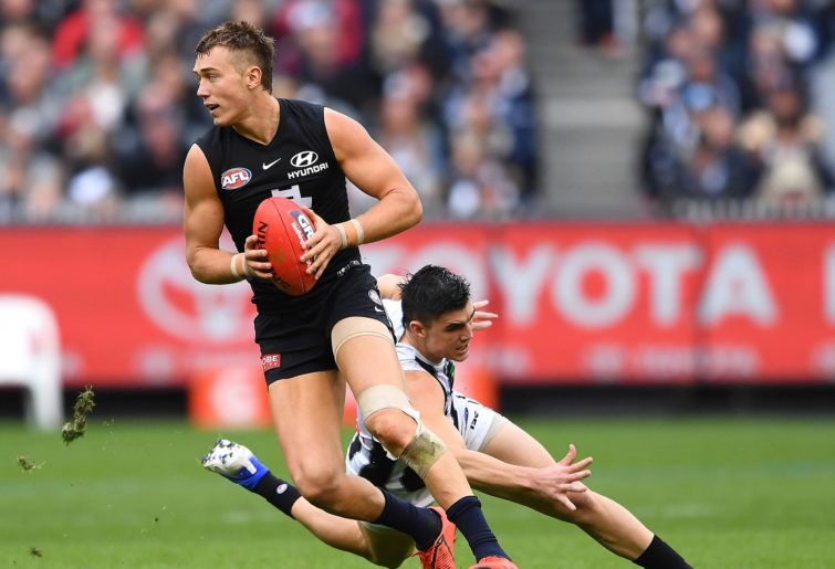 Patrick Cripps of the Blues avoids a tackle by Brayden Maynard of the Magpies