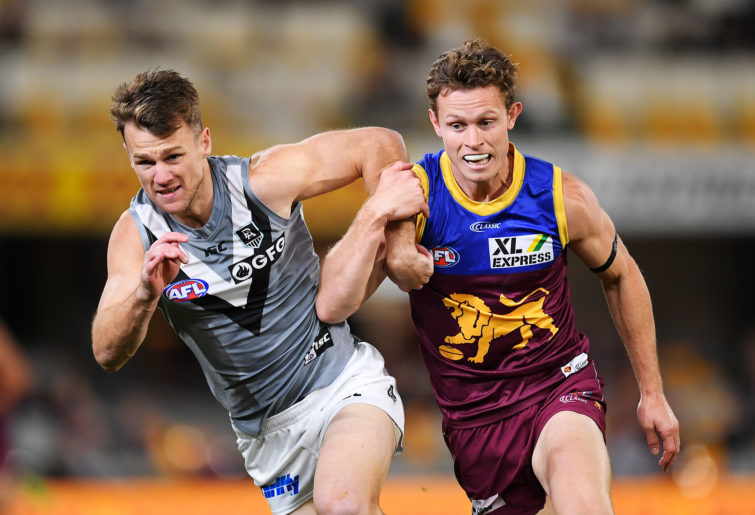 Robbie Gray of the Power and Ryan Lester of the Lions chase after a ball