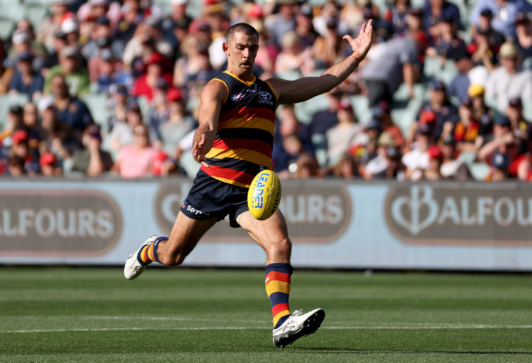 Taylor Walker of the Crows kicks the ball
