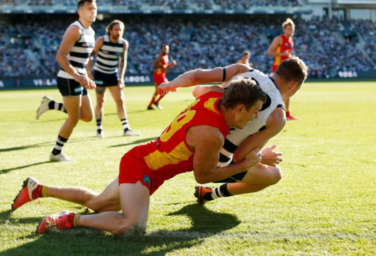 Nick Holman of the Suns tackles Mitch Duncan