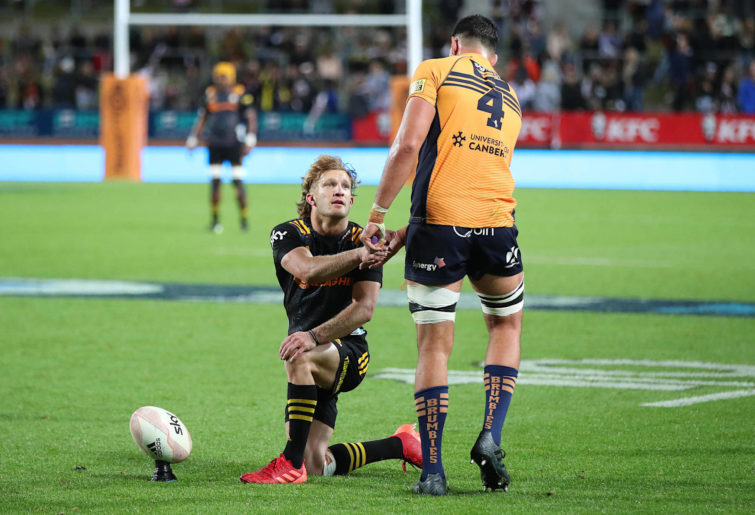 Damian McKenzie of the Chiefs shakes the hand of Darcy Swain of the Brumbies.
