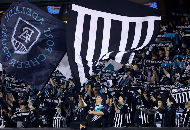 Port Adelaide fans dress in traditional prison bar jerseys
