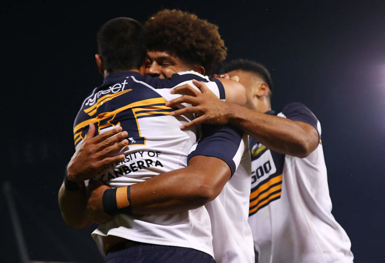 Tom Wright of the Brumbies celebrates scoring a try with teammates.