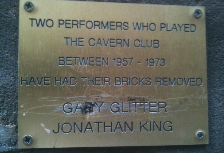 """Gold plaque on a wall reading """"Two performers who played the Cavern Club between 1957 – 1973 have had their bricks removed Gary Glitter Jonathan King"""""""