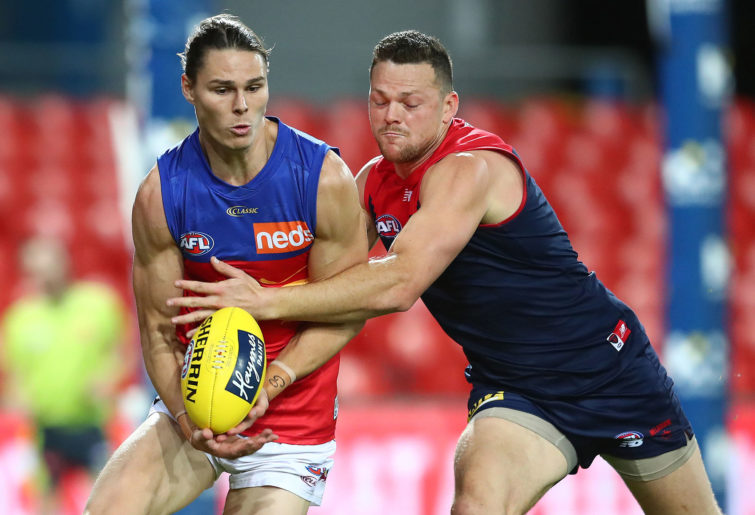 Eric Hipwood of the Lions is tackled by Steven May of the Demons