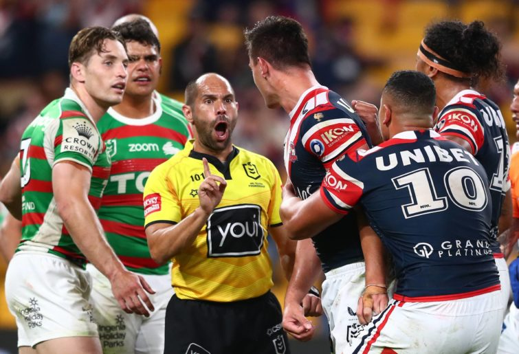 Referee Ashley Klein speaks to Joseph Manu of the Roosters after receiving a high tackle from Latrell Mitchell of the Rabbitohs